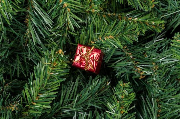 Czerwony prezent na boże narodzenie na białym tle na gałęzi choinki.