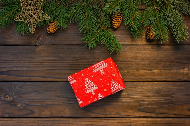 Czerwony prezent na brązowym tle drewnianych. widok z góry.