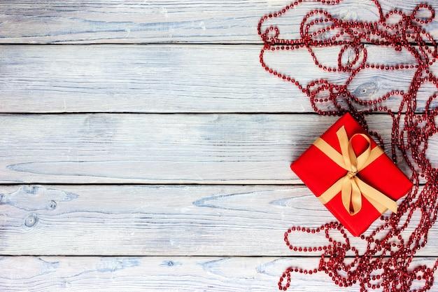 Czerwony prezent przewiązany żółtą wstążką na jasnym drewnianym tle w stylu prowansji.