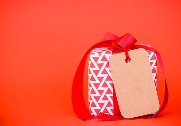 Czerwony prezent pudełko z etykietki karty kopii przestrzenią na czerwonym tle.
