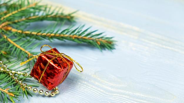 Czerwony prezent z zabawkami choinkowymi i gałązką świerku. skopiuj miejsce