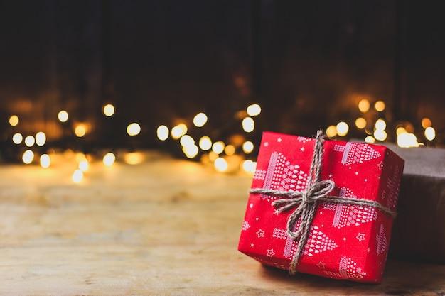 Czerwony prezent związany sznurkiem na drewnianym stole. na tle rozmytych świateł.