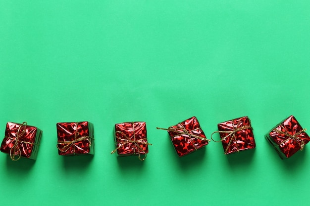 Czerwony prezenta pudełko bożenarodzeniowa dekoracja na zielonym sztuka papieru tle.