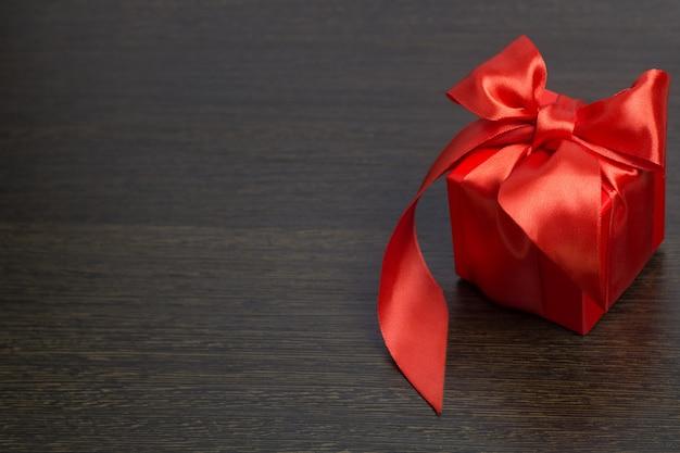Czerwony prezenta pudełko z czerwonym atłasowym tasiemkowym odgórnym widokiem