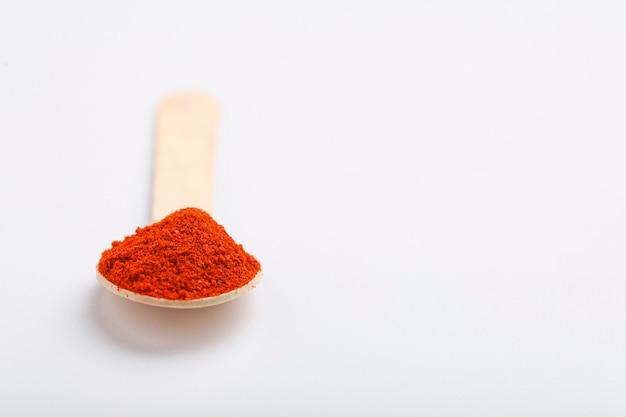Czerwony proszek chili w łyżce na białej powierzchni