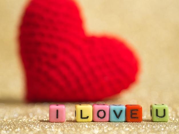 Czerwony przędzy serce z tekstem kocham cię z koralik kolorowe i tło