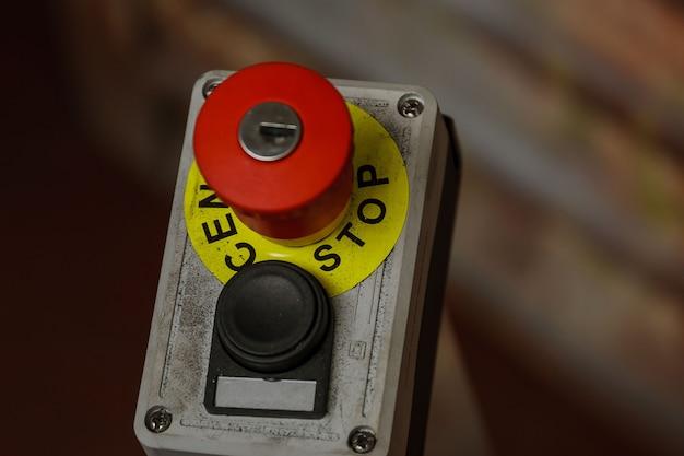 Czerwony przycisk z napisem stop. przycisk zatrzymania awaryjnego z kluczykiem.