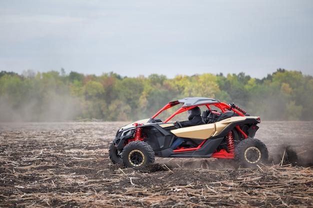Czerwony quad z kierowcą na zaoranym polu