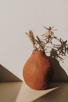Czerwony ręcznie robiony gliniany doniczka z bukietem suchych żyta pszenicy w cieniach słonecznych na białym tle