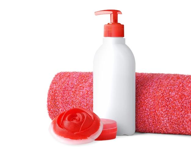 Czerwony ręcznik, butelka mydła w płynie i paski mydła ręcznie robione w kształcie róży na białym tle