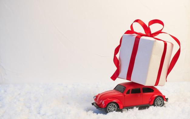 Czerwony retro autko dostarczający prezenty świąteczne lub noworoczne na dachu na śnieżnobiałym tle