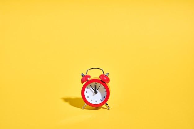 Czerwony retro budzik na żółtym tle. koncepcja minimalnego czasu. wigilia bożego narodzenia lub nowego roku. . wysokiej jakości zdjęcie