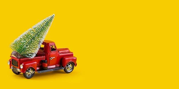 Czerwony retro zabawka ciężarówka z choinką na ciele ciężarówki na żółtej ścianie. dostawa, boże narodzenie, koncepcja nowego roku. vintage model samochodu zabawka z choinką kopiowanie miejsca.