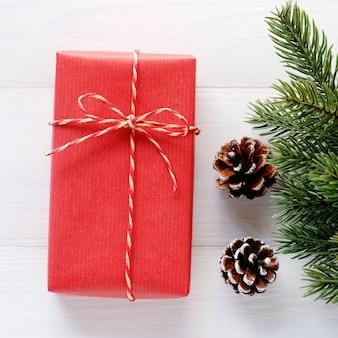 Czerwony rocznika prezenta pudełko i ornament na białym drewnianym tle, bożenarodzeniowy kartka z pozdrowieniami