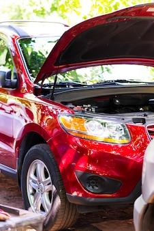 Czerwony samochód hyundai w naprawie z otwartą maską na ulicy