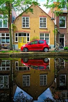 Czerwony samochód na nasypie kanału na ulicy delft delft w holandii