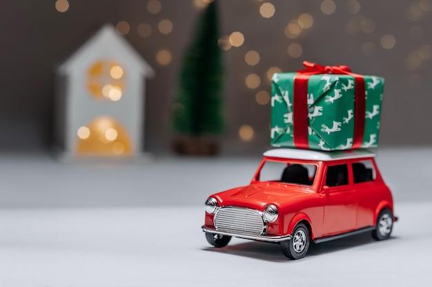 Czerwony samochód na tle lasu i domu przyniesie świąteczne prezenty noworoczne.