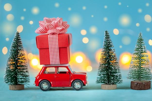 Czerwony samochód niosący na dachu pudełko i choinkę. koncepcja bożego narodzenia i nowego roku