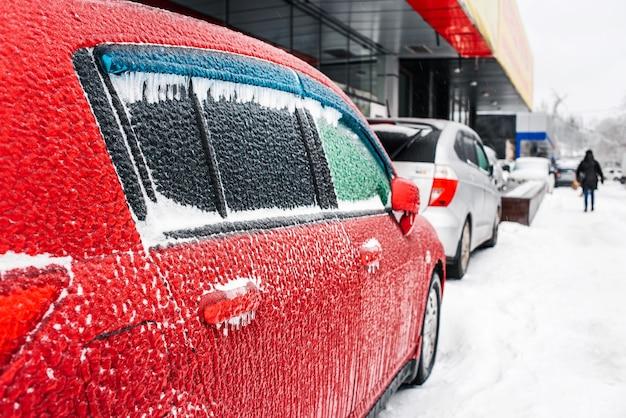 Czerwony samochód pokryty lodem i soplami po marznącym deszczu cyklon burzy lodowej śnieżna pogoda zimowe mroźne sceny