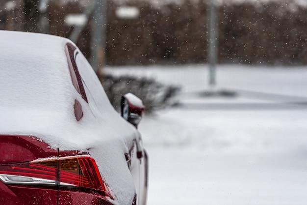Czerwony samochód pokryty śniegiem po burzy, zbliżenie, selektywna ostrość, skupienie na tylnych światłach