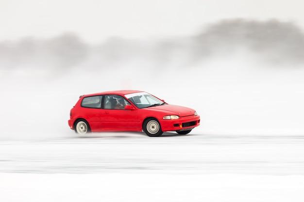 Czerwony samochód poruszający się po lodzie, rozpryskujący się dużo lodu
