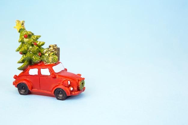 Czerwony samochód retro niesie choinkę z pudełkami prezentowymi na dachu