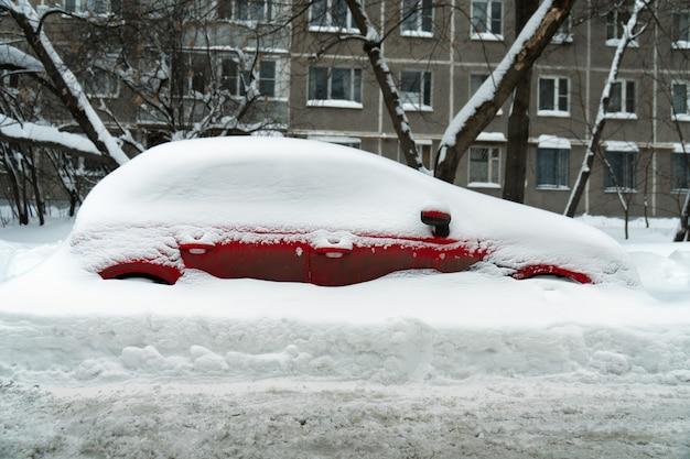 Czerwony samochód stoi w głębokiej zaspie śnieżnej po silnej burzy śnieżnej na poboczu moskiewskiej ulicy zimą