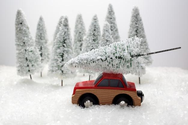 Czerwony samochód wiozący choinkę w pokrytym śniegiem miniaturowym wiecznie zielonym lesie