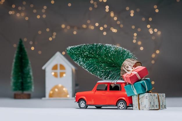 Czerwony samochód z choinką na dachu. na tle domu. koncepcja na temat bożego narodzenia i nowego roku.
