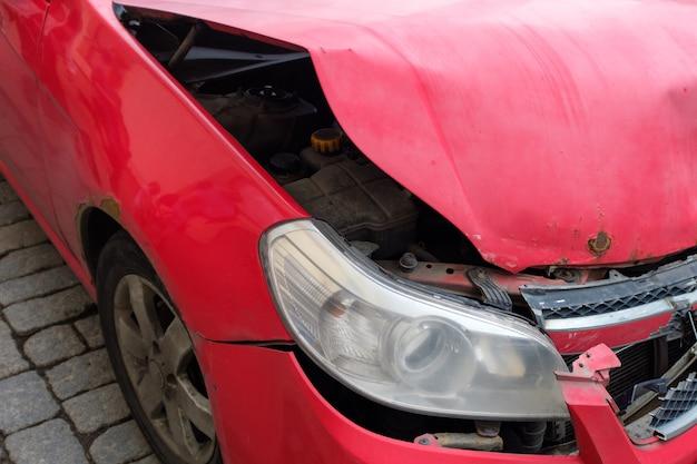 Czerwony samochód z urwaną maską. zbliżenie