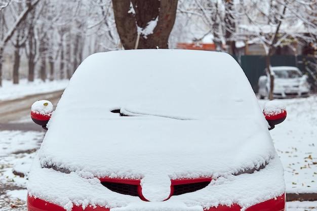 Czerwony samochód zaparkowany na ulicy w zimowy dzień, widok z tyłu. makieta do naklejek lub kalkomanii
