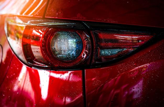 Czerwony samochód ze sportem i nowoczesnym designem myje wodą.