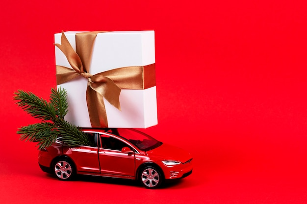 Czerwony samochodzik z pudełkiem i gałęzią jodły