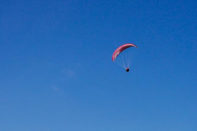 Czerwony samolot leci po błękitnym niebie
