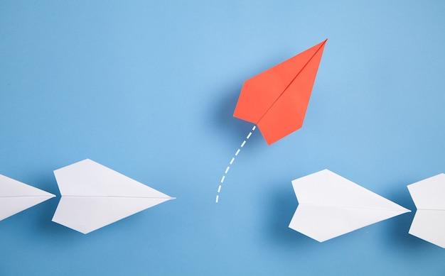 Czerwony samolot zmienia kierunek. myśl inaczej. biznes. nowy pomysł. kreatywność