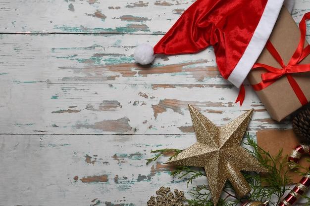 Czerwony santa hat i pudełka na prezenty świąteczne na drewniane tła.