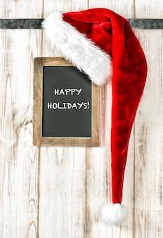 Czerwony santa kapelusz i rocznika chalkboard z przykładowym tekstem szczęśliwi wakacje! dekoracja świąteczna w stylu retro
