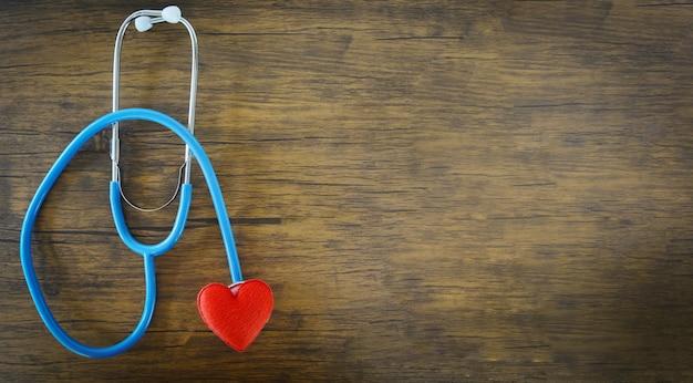 Czerwony serce na stetoskopie na drewnianym tle
