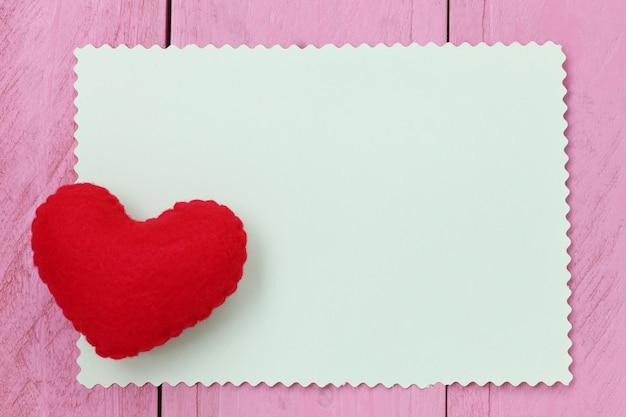 Czerwony serce umieszczający na papier notatce pusty dla wkładu teksta lub wiadomości w projekcie.