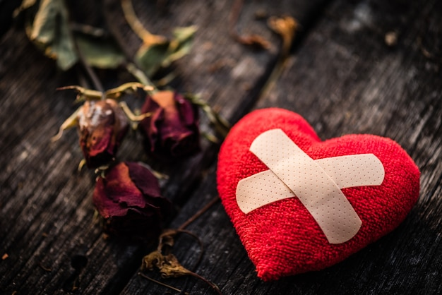 Czerwony serce z wysuszoną czerwieni różą na drewnianym tle. serce złamane