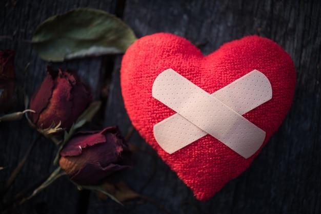 Czerwony serce z wysuszoną czerwieni różą na drewnianym tle. złamane serce koncepcji.