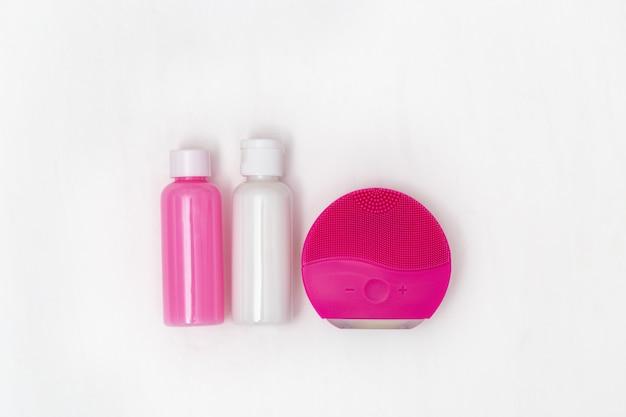 Czerwony silikonowy pędzel i żel do mycia skóry. akcesoria do głębokiego oczyszczania skóry. koncepcja piękna i pielęgnacji skóry.