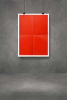 Czerwony składany plakat wiszący na ciemnej betonowej ścianie z klipsami. pusty szablon makiety