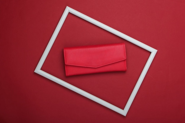 Czerwony skórzany portfel w białej ramce na czerwonej powierzchni