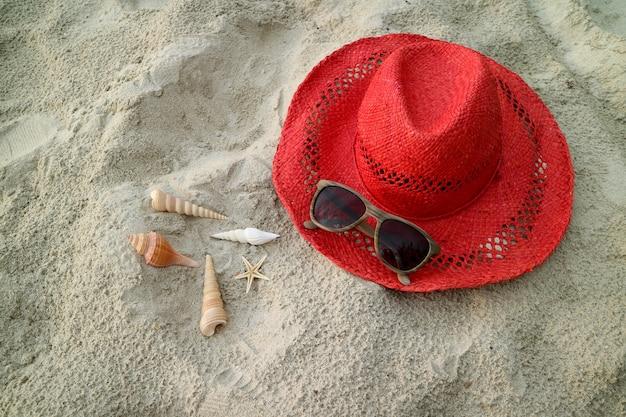 Czerwony słomkowy kapelusz z okularami przeciwsłonecznymi i muszelkami na piaszczystej plaży