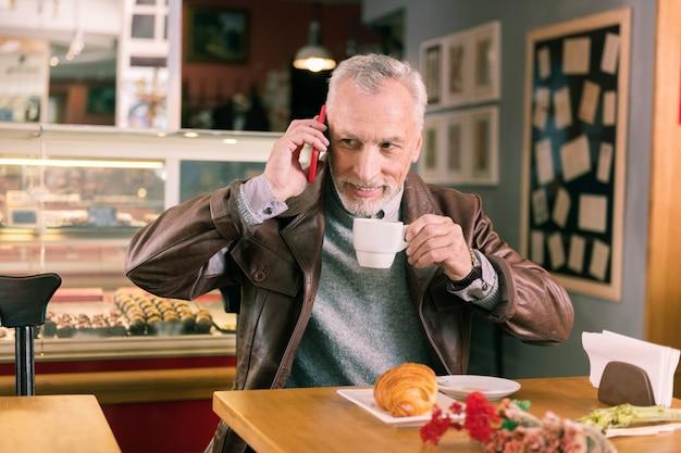 Czerwony smartfon. rozpromieniony troskliwy mąż trzymający swój czerwony smartfon, dzwoniąc do żony, pytając o jej dzień