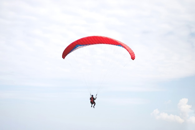 Czerwony spadochron lądujący w wietrzny dzień.
