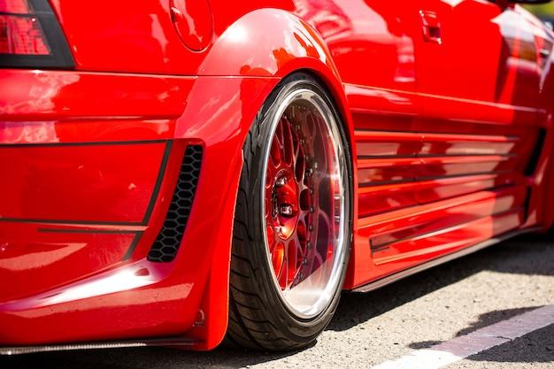 Czerwony sportowy tuningowany samochód widok z tyłu koła, zbliżenie