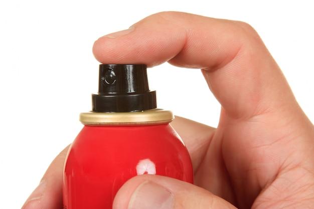 Czerwony sprayem w ręku na białym tle