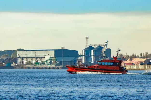 Czerwony statek pilotowy mija fabrykę na łotwie
